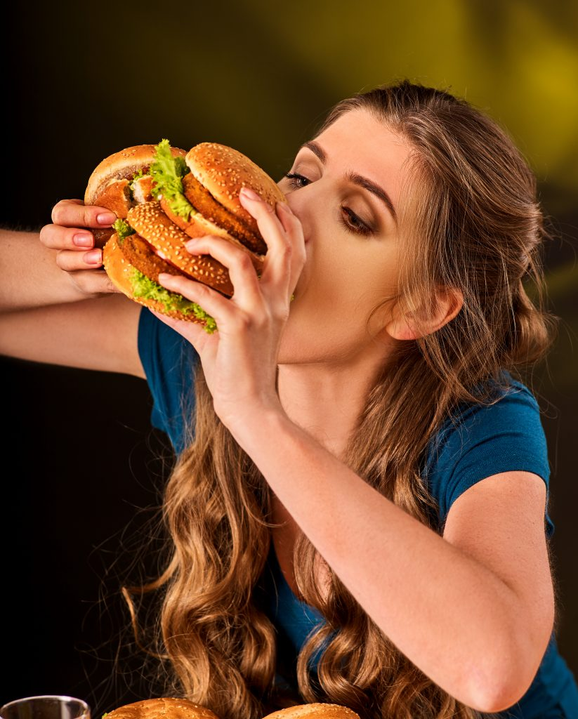Woman eating hamburger. Student consume fast food on table. Girl trying to eat junk on dark background. Cook teaches cook and shares recipes. Expensive fast food restaurant.