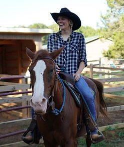Katie Hudgens riding horses smiling